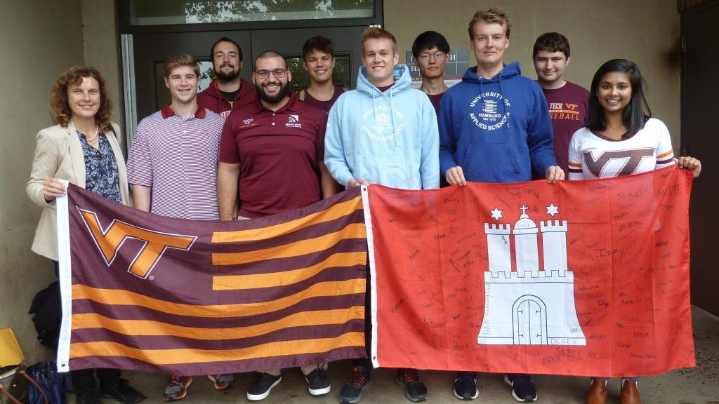 Group of students with professor holding university flags