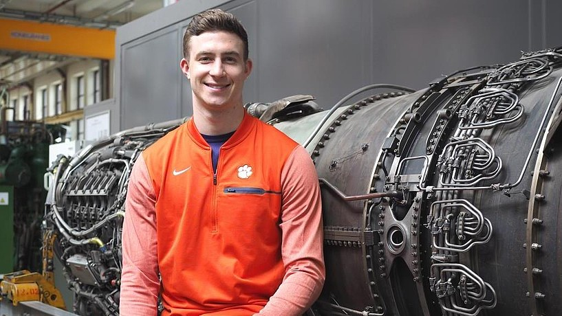Smiling student in front of an aircraft engine