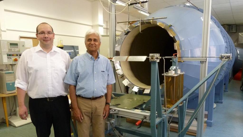 Two male professors in front of a wind tunnel