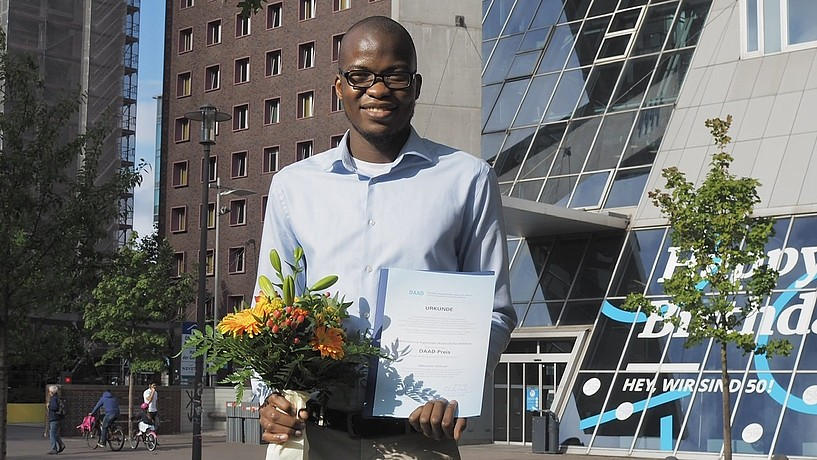 African student with prize certificate in front of university building