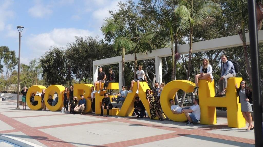 Group of students sitting on large letters that spell Go Beach